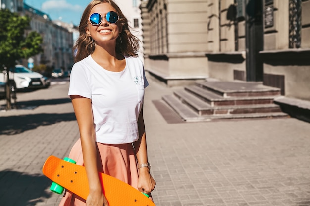 Beautiful cute smiling blond teenager model in summer hipster clothes with orange penny skateboard posing