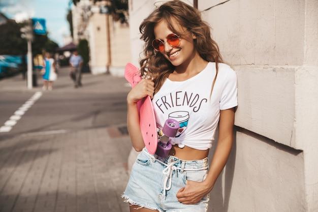 通りの背景にポーズをとってピンクのペニースケートボードと夏流行に敏感な白い服でメイクなしの美しいかわいい笑顔金髪ティーンエイジャーモデル