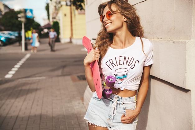 Красивая милая улыбающаяся белокурая модель подростка без макияжа в летней хипстерской белой одежде с розовым скейтбордом копейки позирует на фоне улицы