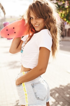 Beautiful cute smiling blond teenager model without makeup in summer hipster white clothes with pink penny skateboard posing on the street background