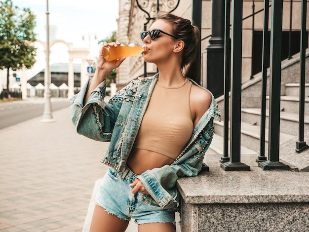 通りでポーズをとる夏のヒップスタージーンズジャケット服の美しいかわいいティーンエイジャーモデル