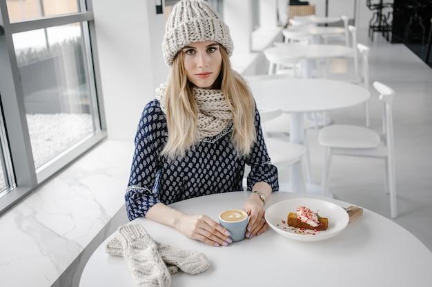 コーヒーマグとニット帽とミトンを身に着けている美しいかわいい冬の女の子。カフェの背景に温かい飲み物を持つ魅力的な女の子。コーヒーを飲みながら人生を楽しむ。
