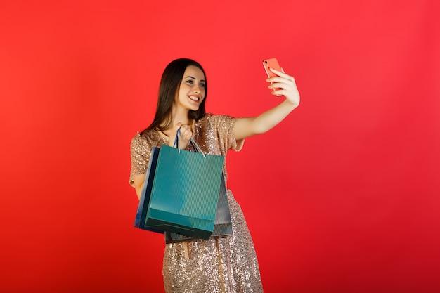 美しいかわいい女性は、カラーの買い物袋で彼女の携帯電話で自分撮りを取ります