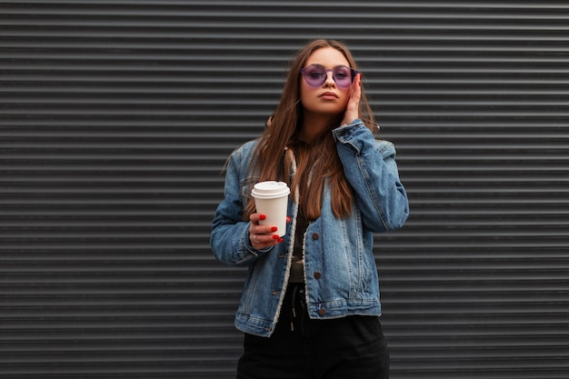 Beautiful cute young hipster woman in fashionable denim blue jacket in trendy purple glasses with cup of hot coffee is posing near a gray wall in the city. urban sexy girl posing model on the street.