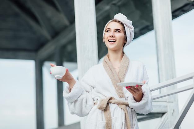 흰색 가운을 입은 아름답고 귀여운 젊은 여성은 커피 한 잔과 함께 고급 테라스에 머물러 있습니다. 산에서 휴가입니다.