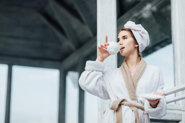 Beautiful,cute young woman wearing at white robe stay on luxury terrace drinking coffee or tea. vacation in mountains.