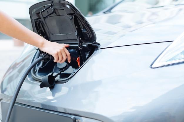 전기 노즐을 잡고 최첨단 전기 자동차를 충전하는 아름다운 우아한 여성 손