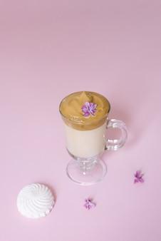 美しいダルゴンコーヒードリンク泡とライラックの花と透明なガラスのコーヒーマグ