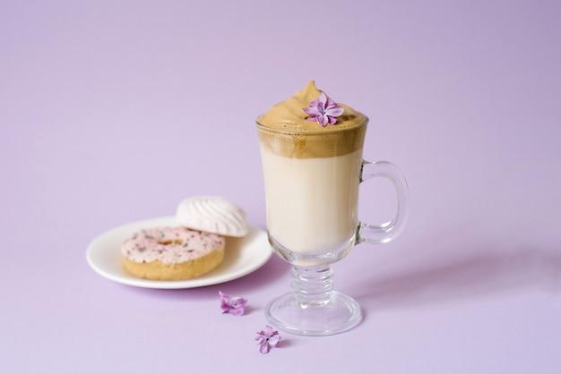 美しいダルゴナは、紫色の背景に透明なマグカップとライラックの花で泡立つコーヒーを飲みます。皿の上のお菓子:ドーナツと甘いマシュマロ