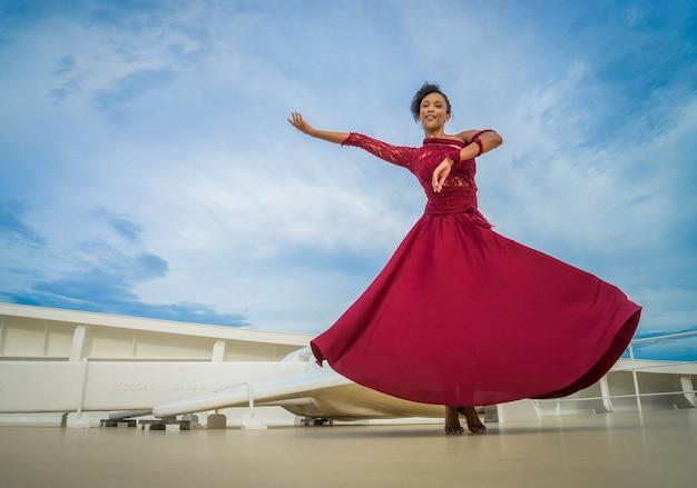 풀과 앵커와 함께 우주선의 뱃머리에 춤 빨간 드레스를 입고 검은 머리를 가진 아름 다운 댄서.