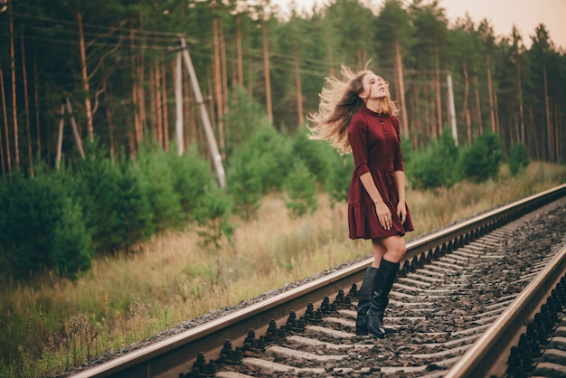 Beautiful dancing girl with curly natural hair enjoy nature in forest on railway. dreamer lady in burgundy dress walk on railroad. dance of inspired girl with hair explosion. sun in hair in autumn.