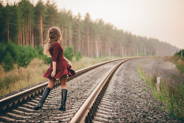 Beautiful dancing girl with curly natural hair enjoy nature in forest on railway.