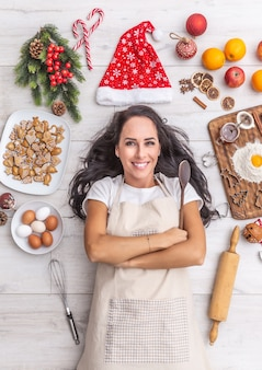 Beautiful dark haired cook laying and widely smiling on the ground, holding the wooden spoon and being surrounded by gingerbreads, eggs, flour, christmas hat and fruit.