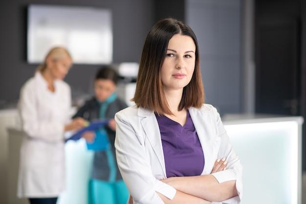 Красивый темноволосый доктор в белом халате выглядит серьезно