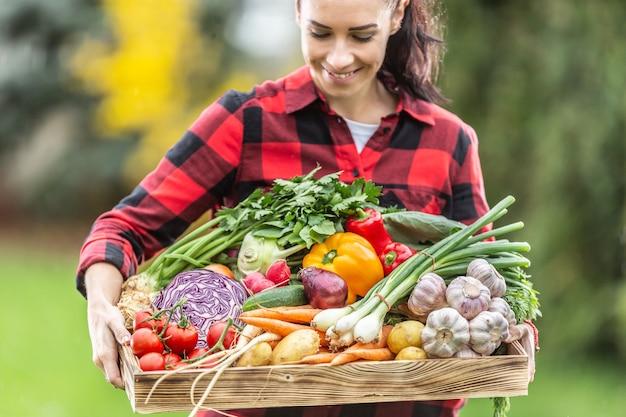 庭から新鮮な健康的な自家製野菜でいっぱいの木製のバスケットを保持している美しい黒髪の農家の女性。