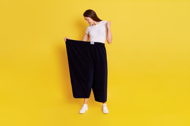 Beautiful dark haired female with perfect body wearing old black pants too big size, lady being glad to loose weight, clenches fist and looks at her trousers, isolated over yellow wall.