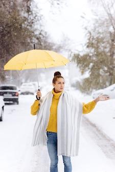 Красивая темноволосая девушка, одетая в желтый свитер, джинсы и белый шарф, стоит с желтым зонтиком на заснеженной улице в зимний день.