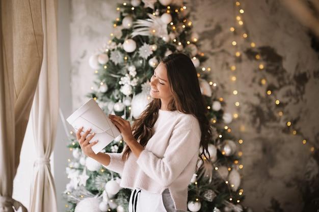흰 스웨터와 바지를 입은 아름다운 검은 머리 소녀가 새해 나무 배경의 창문 옆에 서서 선물을 들고 있습니다.