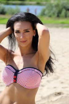Beautiful dark-haired girl in a swimsuit on the beach
