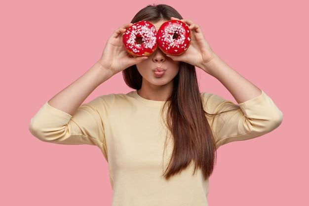 Beautiful dark haired lady keeps both doughnuts near eyes, keeps lips rounded