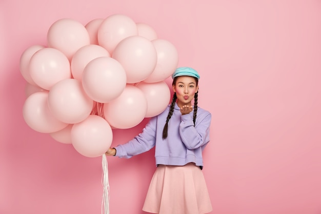 Beautiful dark haired lady with specific appearance, wears makeup, keeps lips rounded, blows air kiss at camera, has flirty expression, poses with helium balloons, isolated over pink wall