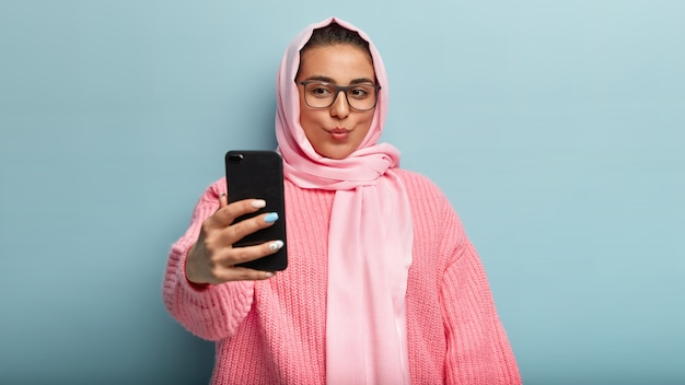 Bella signora musulmana dai capelli scuri registra video, tiene le labbra piegate, scatta selfie, cattura una nuova prospettiva, posa con sciarpa e maglione rosa, pubblica foto online per i follower, fa belle foto al chiuso