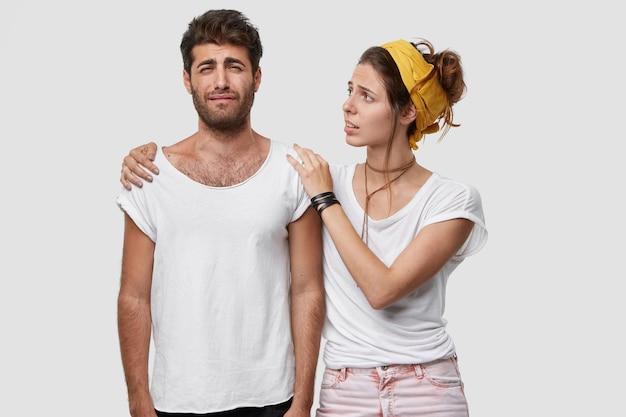 Bella donna dai capelli scuri calma il marito sconvolto che ha problemi, espressioni facciali miserabili, tiene le mani sulle spalle, sta vicino al muro bianco