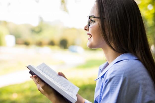La bella donna dai capelli scuri con gli occhiali legge il libro contro il parco verde estivo.