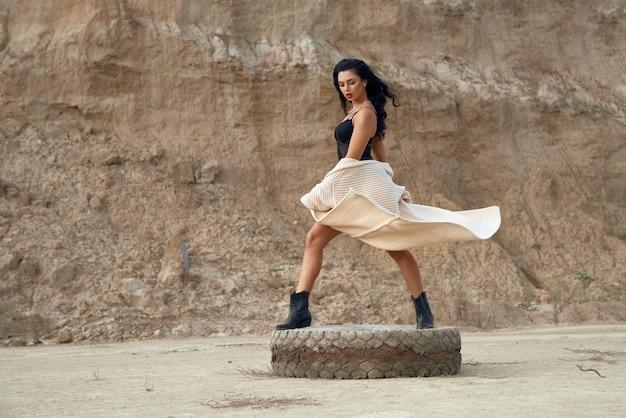 야외에서 오래 된 자동차 타이어에 서 세련 된 섹시 한 bodywear에서 아름 다운 검은 머리 여자