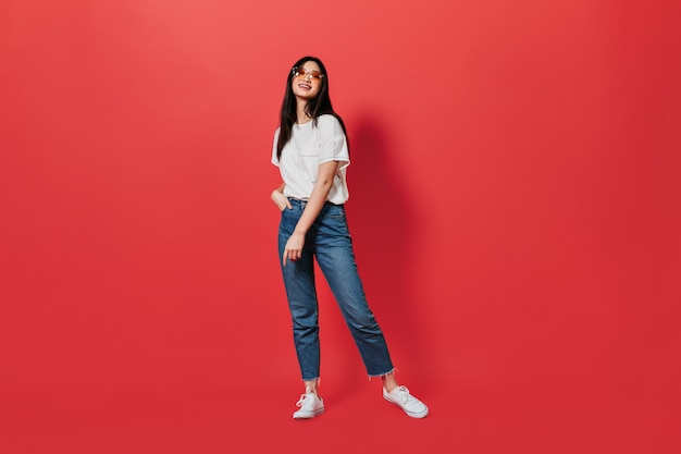 Beautiful dark-haired woman in loose jeans and white t-shirt posing on red wall