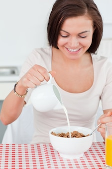 Beautiful dark-haired woman pouring milk in her cereal
