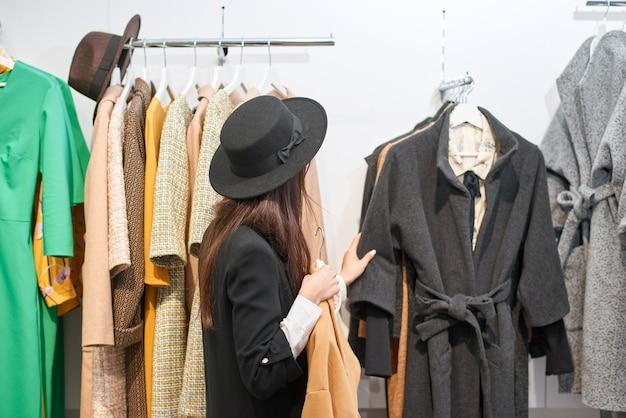 Красивая темноволосая женщина делает покупки для одежды в торговом центре