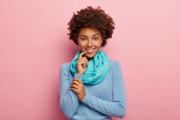 美しい黒髪の女性が活発に話し、友人と楽しいことを話し合い、青いジャンパーとスカーフを身に着け、人差し指で唇に触れます