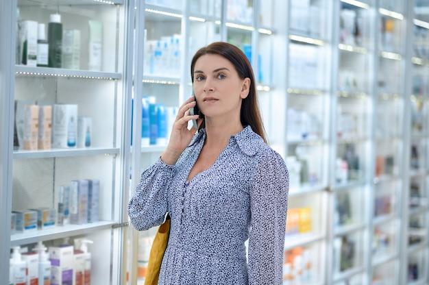 미용 제품이 있는 약국 진열장 옆에 스마트폰을 들고 있는 아름다운 검은 머리 여성