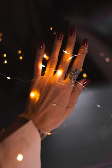 Beautiful dark photo of womans hand fingers with big silver ring on of flowers and glowing lights