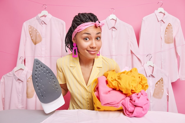 Beautiful dark skinned afro american woman wears headband carries basket full of washed laundry holds electric iron busy doing ironing poses near ironed shirts on hangers against pink wall