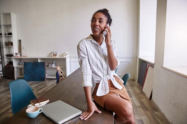 Красивая темнокожая бизнесвумен в повседневной одежде сидит на столе, приятно разговаривает по мобильному телефону, смотрит в сторону и весело улыбается