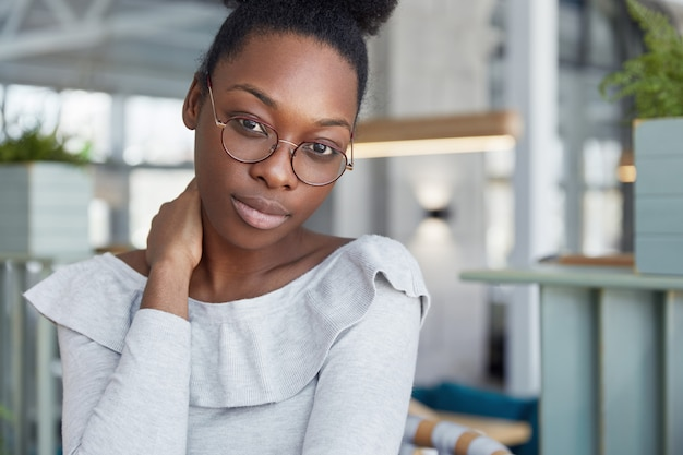 Beautiful dark skinned clever female student in big round eyewear, feels tired after preparing for exams, looks confidently into camera.