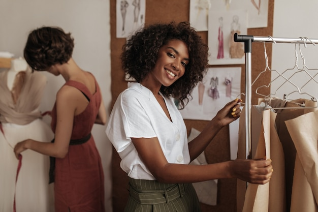 Beautiful dark-skinned curly woman in white blouse smiles, looks at front and works as fashion designer with her friend