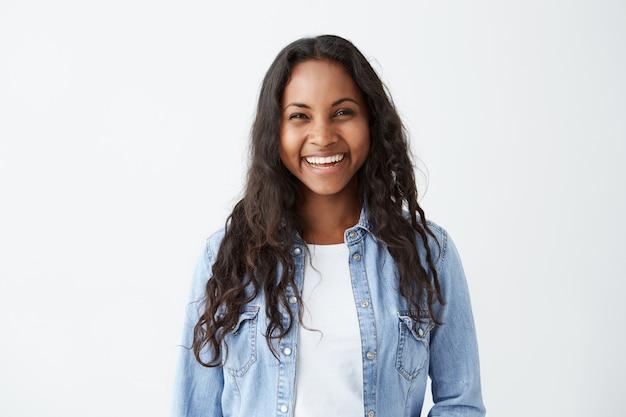 長いブルネットの髪と広い幸せな笑顔で美しい暗い肌の女性、仕事で彼女の昇進に関する良い肯定的なニュースを楽しんでいるデニムシャツを着て、白い空白の壁bに対して隔離されたポーズ