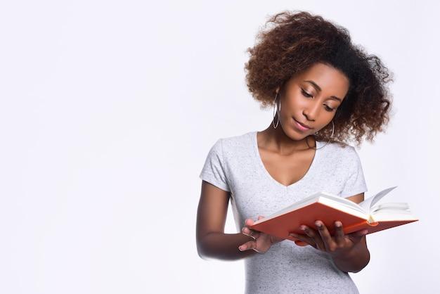 Красивая темнокожая девушка в легкой повседневной футболке читает оранжевую книгу на светлом фоне