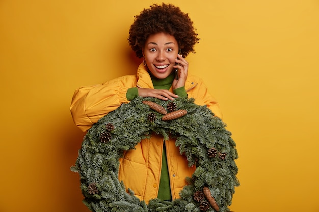 Beautiful dark skinned lady holds handmade christmas spruce fir wreath, has happy expression, wears yellow coat, calls friend, invites to celebrate winter holiday, isolated over yellow background