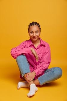 Bella ragazza adolescente dalla pelle scura si siede a gambe incrociate sul pavimento, indossa abiti casual, guarda volentieri, ha riposo, isolato su un muro giallo, trascorre il tempo a casa, felice di fare foto
