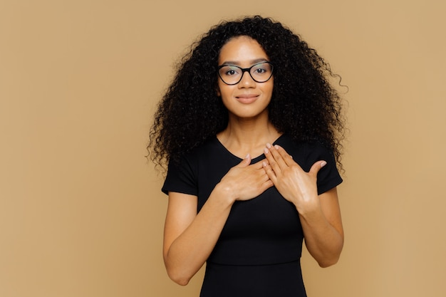 Beautiful dark skinned woman keeps palms near hear, expresses gratitude, thankfulness, has friendly facial expression