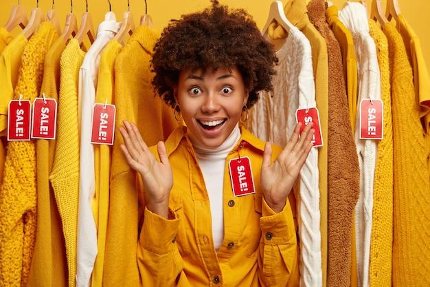 Красивая темнокожая женщина в окружении вешалки для одежды