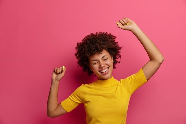 아름답고 어두운 피부를 가진 젊은 여성은 편안하고 안도감을 느끼고, 평온한 춤을 추며, 팔을 공중에 들고, 긍정적으로 미소를 짓고, 캐주얼하게 옷을 입고, 분홍색 벽에 포즈를 취합니다. 행복 한 라이프 스타일 개념