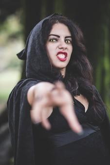 검은 맨틀과 후드와 함께 아름 다운 어두운 뱀파이어 여자