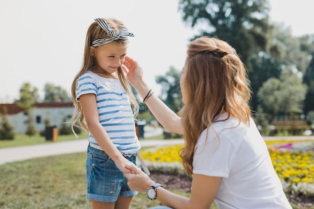 아름다운 딸. 그녀의 아름다운 즐거운 딸을 돌보는 blonde-haired 유행 여자