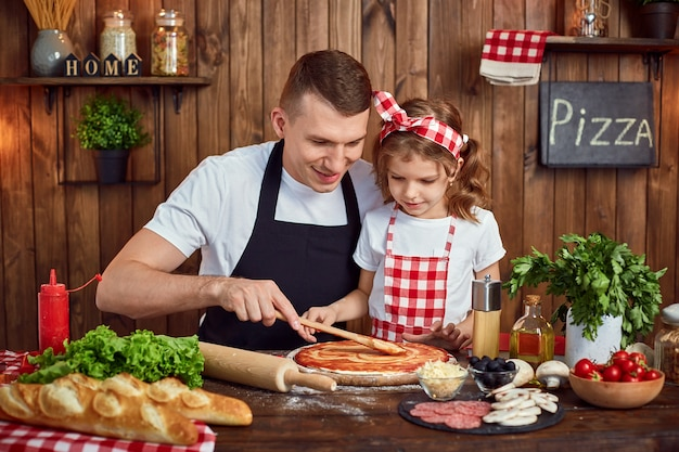 Beautiful daughter helping dad to spread sauce while cooking pizza