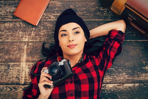 美しい日の夢想家。床に横たわって、スーツケースとメモ帳が彼女の近くに横たわっている間カメラを保持している帽子の美しい若い女性の上面図